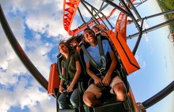 A young woman and man ride ride an orange and black roller coaster called Tigris, Florida's tallest launch coaster located at Busch Gardens Tampa Bay, located in Florida.