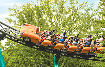 People riding Verbolten roller coaster outside through trees